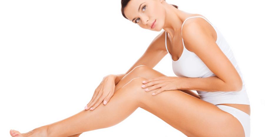 Woman sitting on floor feeling legs