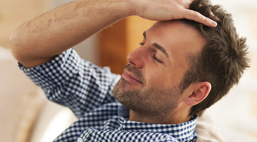 Man combing hair back with hands